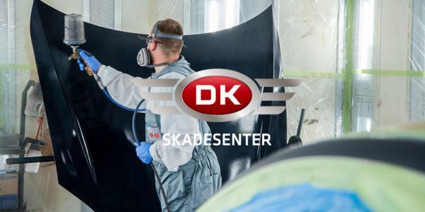 Bilde av mann som spraylakkerer bil, med DK skadesenters logo foran.